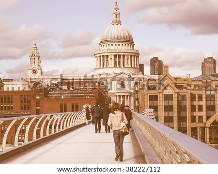 LONDON, ENGLAND, UK - MARCH 04, 2009: Tourists crossing the Millennium Bridge linking the City of London with the South Bank between St Paul Cathedral and Tate Modern art gallery vintage