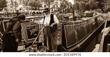 LONDON, ENGLAND, UK - MAY 5, 2014: Unidentified senior couple in vintage costume and their dog participate in Canalway Cavalcade of traditional boats (waterways festival taking place in Little Venice) - stock photo
