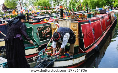 LONDON, ENGLAND, UK - MAY 5, 2014: Unidentified senior couple in vintage costumes participates in Canalway Cavalcade of traditional boats, a unique waterways festival taking place in Little Venice. - stock photo