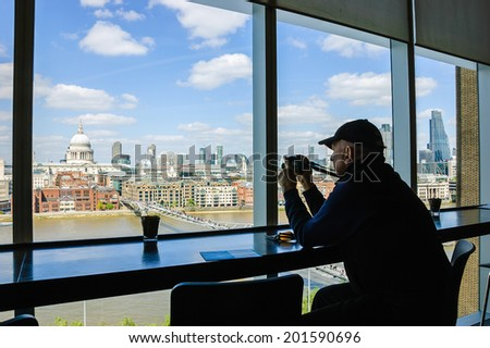 LONDON, ENGLAND, UK - MAY 3, 2014: Unidentified tourist takes picture of  a view on St Paul Cathedral from Tate Modern gallery's cafe. - stock photo