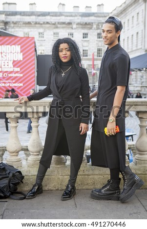 LONDON - FEBRUARY 18: Woman in black dress and man in black suit pose for photographers outside Somerset house during London Fashion week on February 18, 2014.