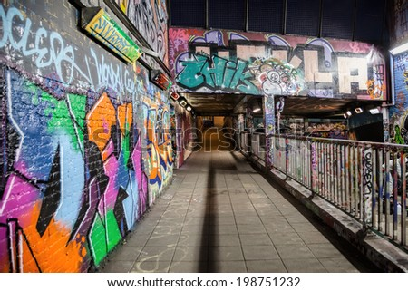 LONDON, GREAT BRITAIN - 18th of January 2014:Unknown artist painting graffiti and pedestrians on the Leake Street in LONDON, GREAT BRITAIN on 18th of January 2014 - stock photo