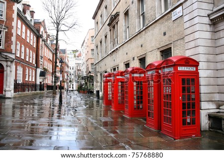 London in the rain - row of red telephone boxes at Broad Court. Covent Garden district. - stock photo