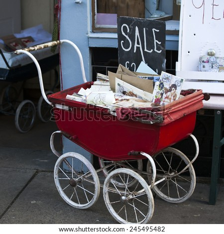 London - January 17, 2015. Flea market window shop with old-fashioned goods displayed in London city, UK. Old baby stroller with letters. on 17 January 2015. windowshop of old shop with antique things - stock photo