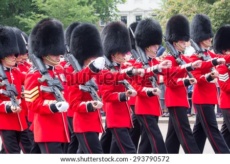 LONDON - JUL 1, 2015: British Royal guards performing the Changing of the Guard at Buckingham Palace. The ceremony is one of the top attractions in London and UK military traditions. - stock photo