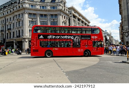 LONDON - JULY 1, 2014: A London red bus bearing Adidas advertisement crossing at Oxford Circus in London.   - stock photo