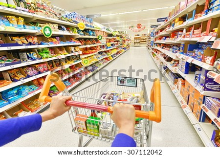 LONDON - JULY 3: A shopper pushes a trolley on an aisle at a Sainsbury's supermarket on July 3, 2014 in London, UK. Sainsbury's is the UK's 2nd largest supermarket with a revenue of £23 bln in 2013. - stock photo