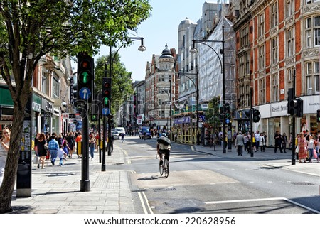 LONDON - JULY 1, 2014. Shoppers and traffic on Oxford street, the biggest shopping street in Europe, visited by millions of tourists. - stock photo
