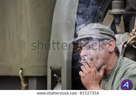 LONDON - JULY 21 - Unidentified member of the public smokes cigarette during WW2 era reenactment at War and Peace show, world's largest military show, on July 21st, 2011 near London, England