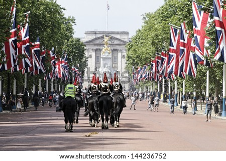 LONDON - JUN 30: The colorful changing of the guard ceremony at Buckingham Palace on June 30th, 2013 in London, UK. It is one of England's most popular visitor attractions. - stock photo