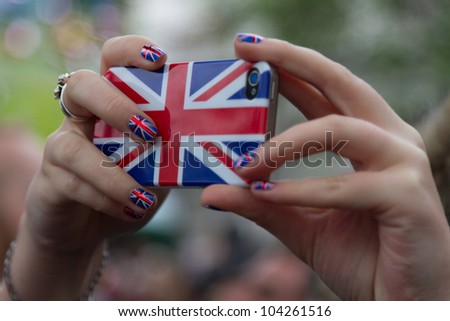 LONDON - JUNE 3: A camera phone is lifted above the crowds to capture a photo as crowds celebrate Thames Diamond Jubilee Pageant on June 3, 2012 in London. - stock photo