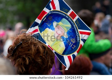 LONDON - JUNE 3: A commemorative flag is shown worn in an unidentified woman's hair as crowds witness the Thames Diamond Jubilee Pageant on June 3, 2012 in London. - stock photo