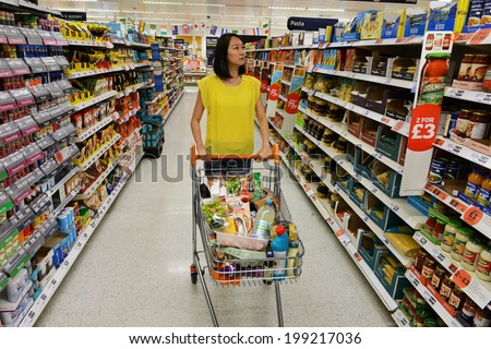 LONDON - JUNE 14: A shopper browses an aisle at a Sainsbury's supermarket on June 14, 2014 in London, UK. Sainsbury's is the UK's second largest supermarket with a revenue of �£23 bln in 2013. - stock photo