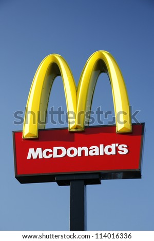 LONDON - JUNE 28: McDonalds logo on blue sky background on June 28, 2012, London, UK. It is the world's largest fast food chain, over 31,000 restaurants worldwide, serve 58 million customers each day - stock photo