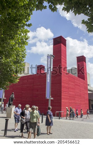 LONDON - JUNE 21. Red timber clad temporary theatre known as 'The Shed' with National Theatre behind, June 21, 2014, at the Southbank, London, UK. - stock photo