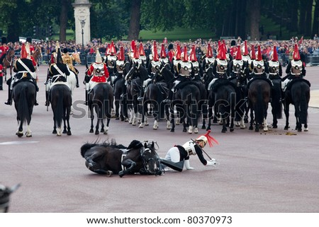 LONDON - JUNE 11: Royals horse Guard falls off horse at Trooping the Color ceremony in London, England on June 11, 2011. Ceremony is performed by regiments on the occasion of the Queen's Official Birthday - stock photo