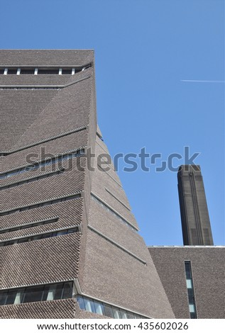 LONDON - JUNE 6, 2016. The angular perforated brickwork of the Tate Modern art gallery extension, designed by Herzog & de Meuron, with the original power station chimney beyond at Bankside, London. - stock photo