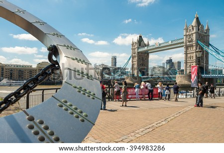 LONDON - JUNE 14, 2015: Tourists near Tower Bridge. London is visited by 50 million people annually.