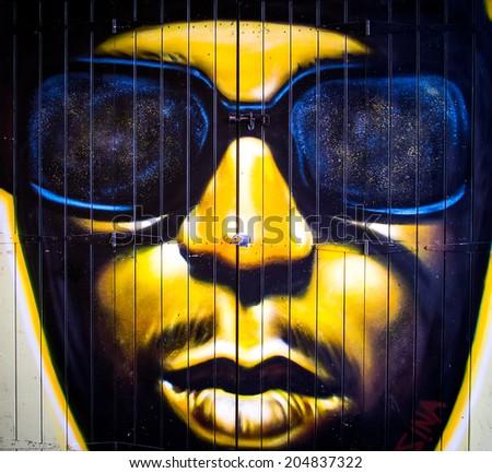 London, June 2014 - urban graffiti near Camden Lock Market. The work is a drawing portrait of man by an unknown artist - stock photo