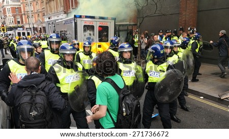 LONDON - MAR 26: Protesters confront riot police at a TUC organised anti cuts rally on Mar 26, 2011 in London, UK. Clashes erupted during the 250,000 strong march through the British capital. - stock photo