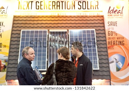 LONDON - MAR 15: visitors ask for information on solar panels to an exhibitor during the Ideal Home Show 2013 in London on March 15, 2013 - stock photo