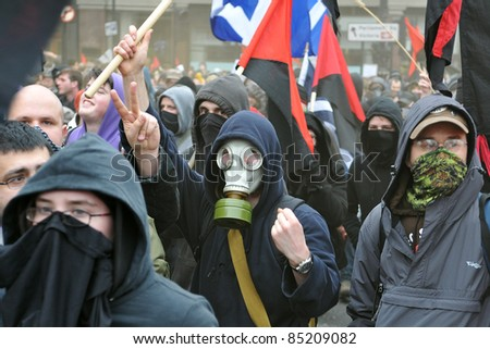 LONDON - MARCH 26: A breakaway group of anarchist protesters march through the streets of the British capital during a large anti-cuts rally on March 26, 2011 in London, UK. - stock photo