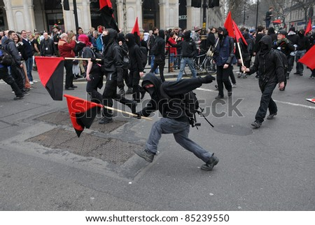 LONDON - MARCH 26: A breakaway group of anarchist protesters march through the streets of the British capital during a large TUC organized anti-cuts rally on March 26, 2011 in London, UK. - stock photo