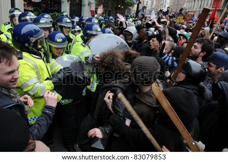 LONDON - MARCH 26: A breakaway group of protesters clash with police on Piccadilly during a large anti-cuts rally on March 26, 2011 in London, UK. - stock photo