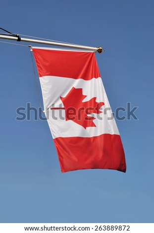LONDON - MARCH 6, 2015. A Canadian national Maple Leaf flag, a bicolour triband design by George Stanley adopted in 1965, flies on the front of Canada House in Trafalgar Square, London, UK. - stock photo