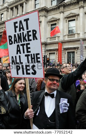 LONDON - MARCH 26: A protester dresses as a banker attends a large anti public sector spending cuts rally organised by the TUC March 26, 2011 in London, UK. - stock photo