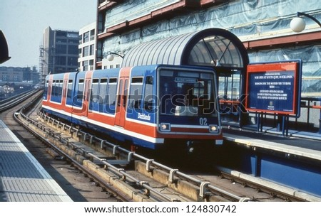 LONDON - MARCH 30: An automatic Electric Multiple Unit train arrives at South Quay station on the Docklands Light Railway on March 30, 1990 in London. Some 25 miles long, the DLR opened in July 1987.