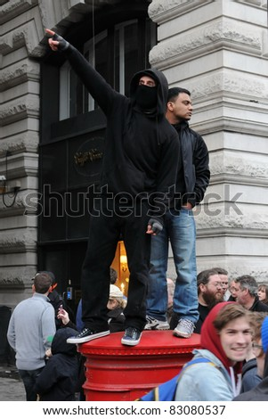 LONDON - MARCH 26: An unidentified masked male directs protesters during a large anti-cuts rally 26 March 2011 in London, UK. - stock photo