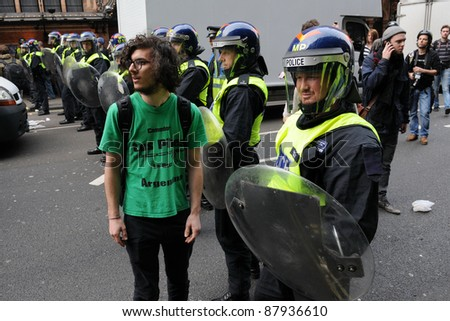 LONDON - MARCH 26: An unidentified protester prevented by riot police from passing a cordon during a large TUC organised anti-cuts rally on March 26, 2011 in London, UK. - stock photo