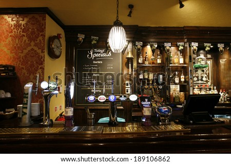 LONDON - MARCH 14: Interior of pub, for drinking and socializing, focal point of community, on March 14, 2014, London, UK. Pub business, now about 53,500 pubs in the UK, has been declining every year  - stock photo