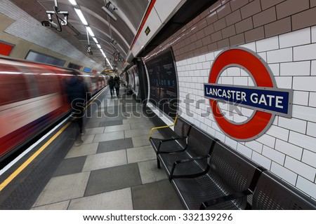 LONDON - MARCH 07, 2015: London Underground sign with moving train and people at Lancaster Gate station. The station is the easy access to tourist attractions; Kensington Palace and Hyde Park. - stock photo
