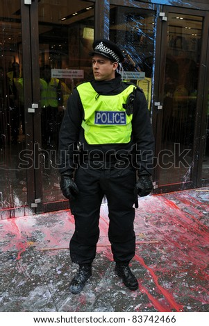 LONDON - MARCH 26: Policeman on duty in central London after having come under attack by a breakaway group of protesters during a large anti-cuts rally on March 26, 2011 in London, UK. - stock photo