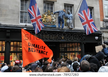 LONDON - MARCH 26: Protesters attending a large TUC organised rally climb along shop fronts on Piccadilly to evade police arrest after briefly occupying a shopping mall March 26, 2011 in London, UK.