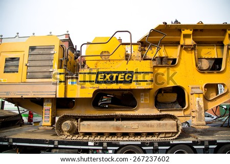 LONDON - MARCH 30TH: A transporter  carries a rock crushing machine on March the 30th, 2015, in London, England, UK. Rock crushers are widely used in construction anmd mining industries. - stock photo