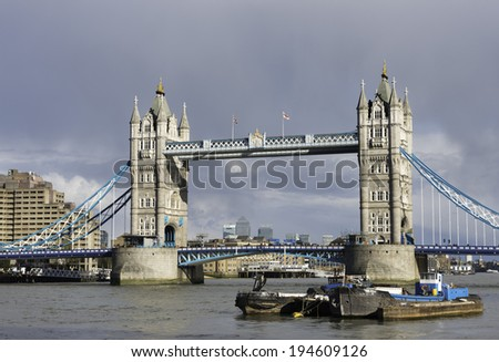 LONDON - MARCH 23: View of the Tower Bridge and the river Thames in London on a cloudy spring day, with locals and tourist walking over the bridge, on March 23, 2014.