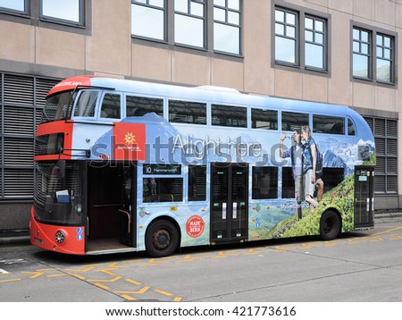 LONDON - MAY 7, 2016. A Routemaster diesel-electric hybrid double deck bus is decorated to promote Switzerland, parked at Hammersmith Bus Station, west London, UK. - stock photo