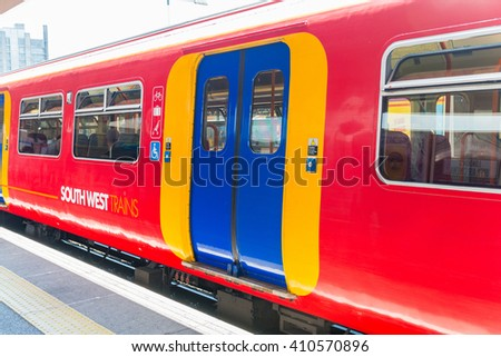 LONDON - MAY 21, 2015: A South West Trains commuter service heads towards Central London. Increasing rail fares are of growing concern in United Kingdom. - stock photo