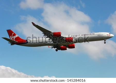 LONDON - MAY 25: A Virgin Atlantic Airbus A340 on approach on May 25, 2013 in London.  Virgin Atlantic Airways is a British airline with 43 planes and 5.5 million passengers in 2012. - stock photo