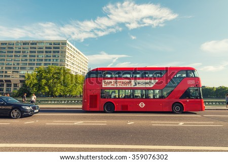 LONDON - MAY 5, 2015: Double Decker bus crossing city streets. It is a city attraction for worldwide tourists. - stock photo