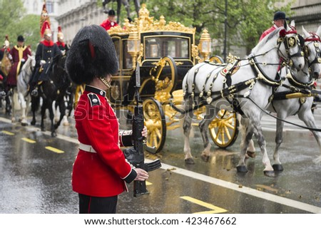 LONDON - MAY 18, 2016: Guard stands at attention as the horse-drawn Diamond Jubilee State Coach carrying Queen Elizabeth II toward Buckingham Palace passes along a rainy street.   - stock photo