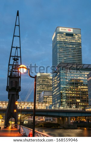 LONDON - MAY 9: HSBC's World Head Quarters building and old port cranes at Canary Wharf at night on May 9, 2011 in London. It is part of the redevelopment around Canary Wharf in the London Docklands. - stock photo