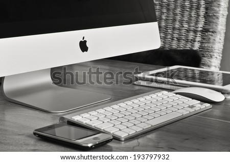 LONDON - MAY 20: iMac monitor and keyboard with iPhone, magic mouse and iPad on a desk in black and white. May 20, 2014 in London, UK. - stock photo