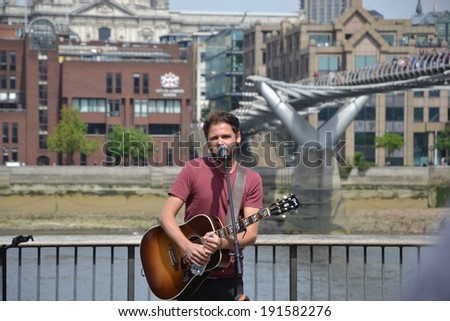 LONDON - MAY 5: Passenger busks on the South Bank in London, UK on May 5, 2014. Best known for the song Let Her Go, Passenger performed a surprise public gig.  - stock photo