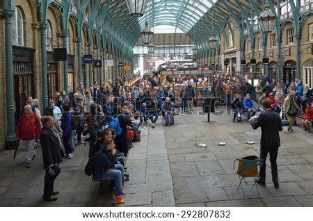 LONDON - MAY 15 2015:Spectators watching street show in Covent Garden in London, UK. Covent Garden is the only district in London to have a license for street performers and entertainers. - stock photo