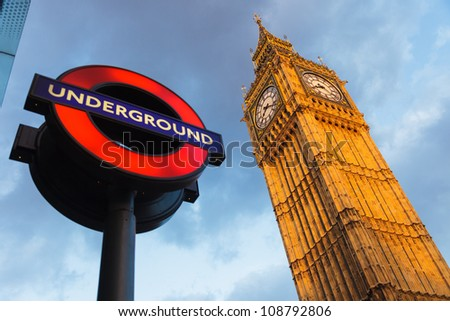 LONDON - MAY 08 :  The 'Underground' sign and 'Big Ben' tower at evening on May 08 2009 in London. The Underground serves 270 stations and has 402 km of track. - stock photo