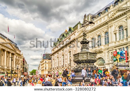 LONDON - MAY 28:Tourists gather around the statue of Eros at Picadilly Circus May 28, 2015 in London. The Circus is close to major shopping and entertainment areas in the West End - stock photo